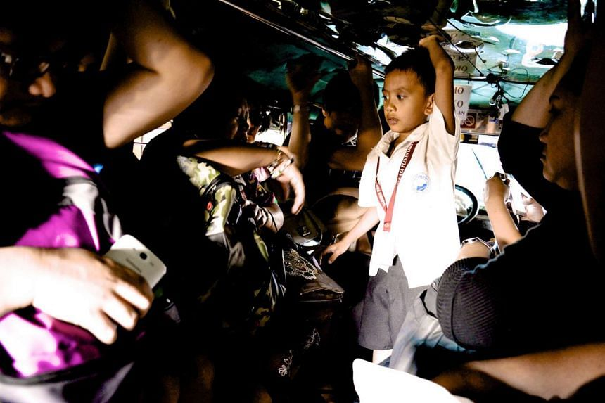 Passengers on board a jeepney in the Philippines are seated closely together, often shoulder to shoulder.