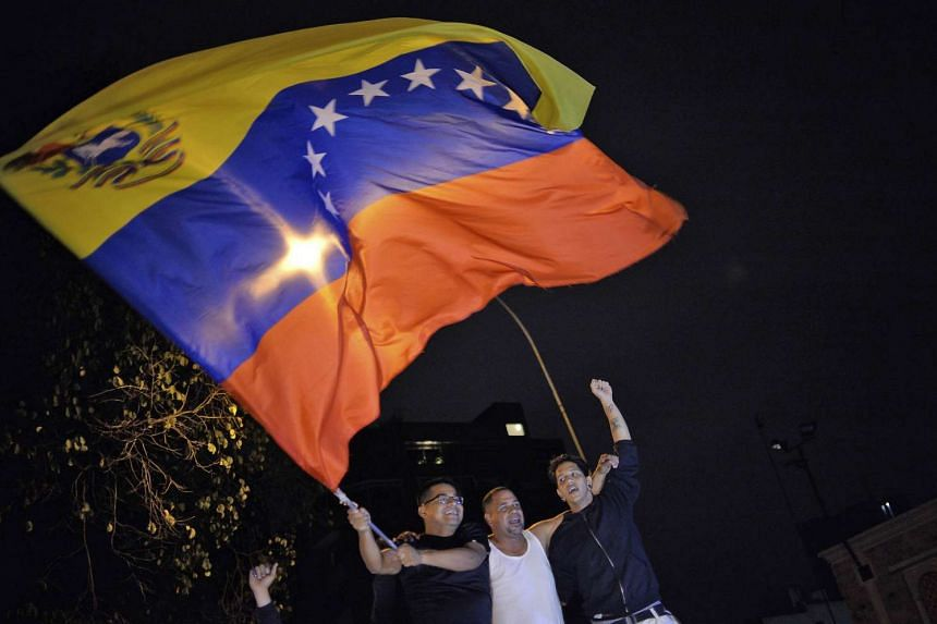 Venezuelan opposition supporters celebrating after the opposition won a majority in the state legislature during elections, in Caracas on Dec 7, 2015.