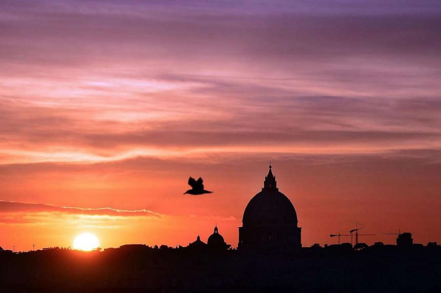 The sun sets behind Saint Peter's Basilica in Rome, as the Jubilee dedicated to mercy announced by Pope Francis is about to get underway.