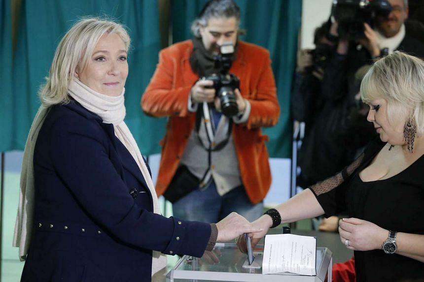 National Front leader Marine Le Pen (in blue) casting her vote yesterday in the first round of French regional elections in Henin- Beaumont in the north. The second round will be on Dec 13.