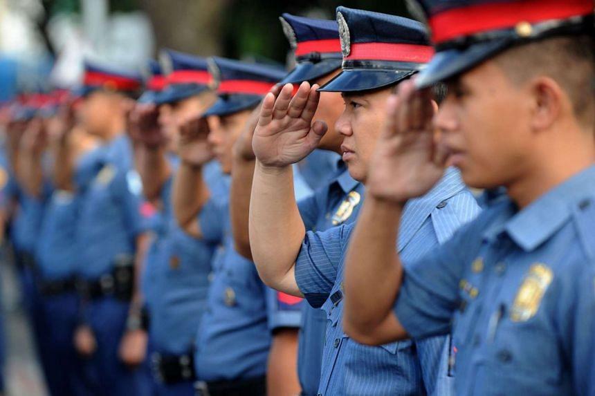 Philippine police salute at Camp Crame in suburban Manila.