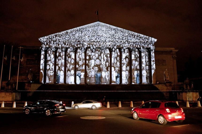 An artwork by French artist JR and US filmmaker Darren Aronofsky is projected onto the French National assembly (Parliament) on Nov 29, 2015.