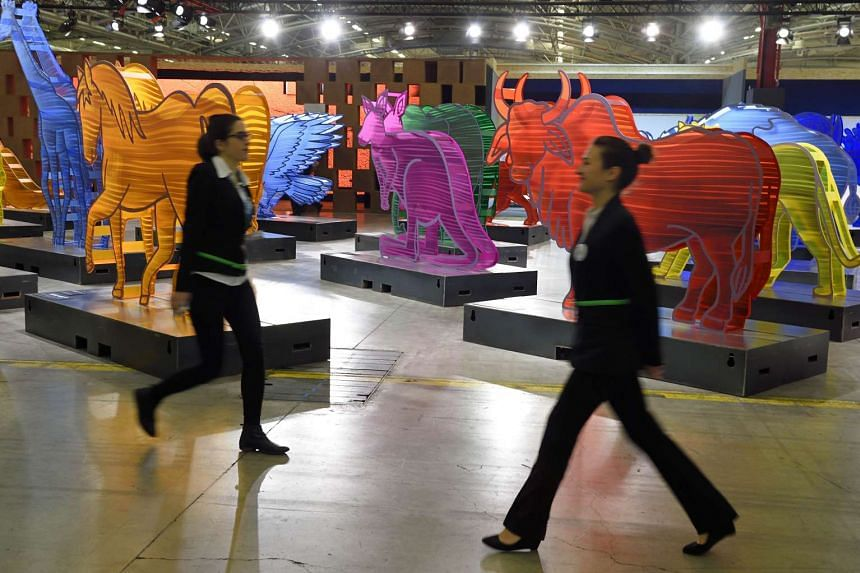 Staff members pass by the Noe-Climat Arch sculpture installation during the UN climate summit on Nov 30, 2015 in Le Bourget, northern Paris. More than 150 world leaders are meeting under heightened security, for the 21st Session of the Conference of