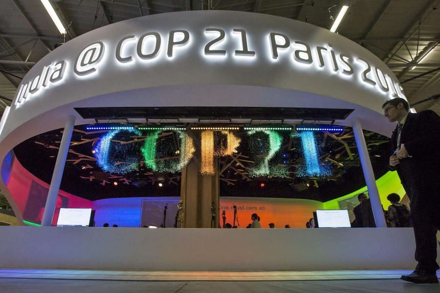A visitor walks past a fountain installation which forms the word 'COP21' during the UN climate summit in Le Bourget, north of Paris, on Dec 3, 2015. The 21st Conference of the Parties (COP21), as the summit is called, aims at reaching an internatio