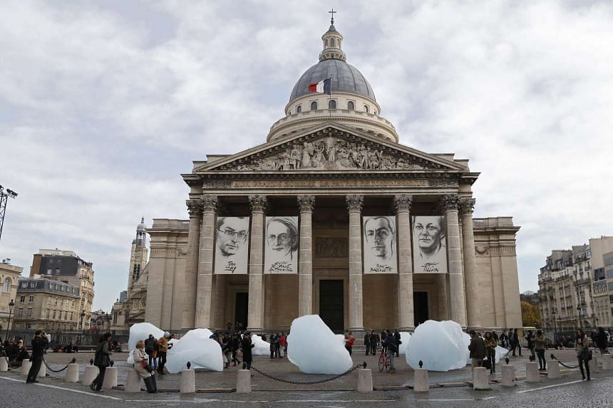 Visitors walks by ice blocks from Greenland as part of an art installation entitled 'Ice Watch Paris' by Danish artist Olafur Eliasson on display in front of the Pantheon in Paris, on Dec 3, 2015.