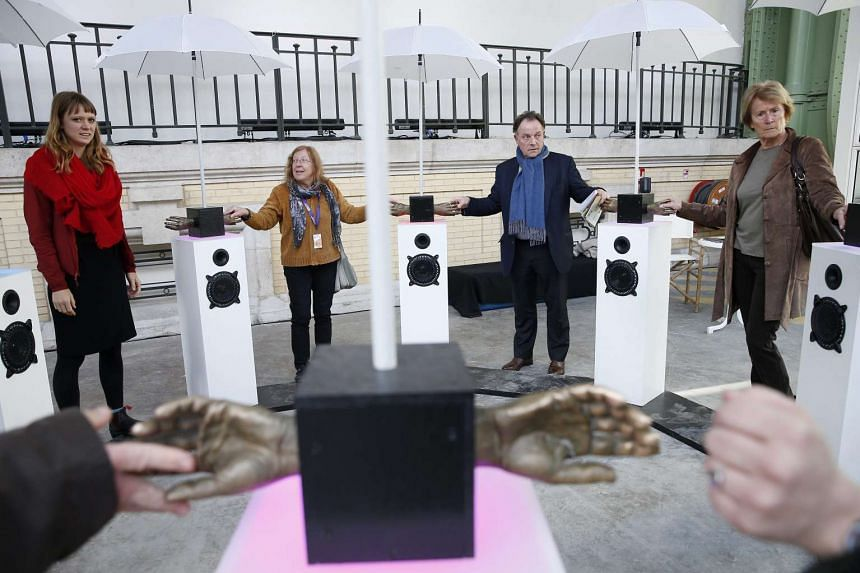 Visitors enjoy an interactive musical installation during their visit to the Solutions COP21 event at Grand Palais in Paris, on Dec 4, 2015. Solutions COP21 takes place at Grand Palais on the sidelines of the UN climate summit, also known as the 21st