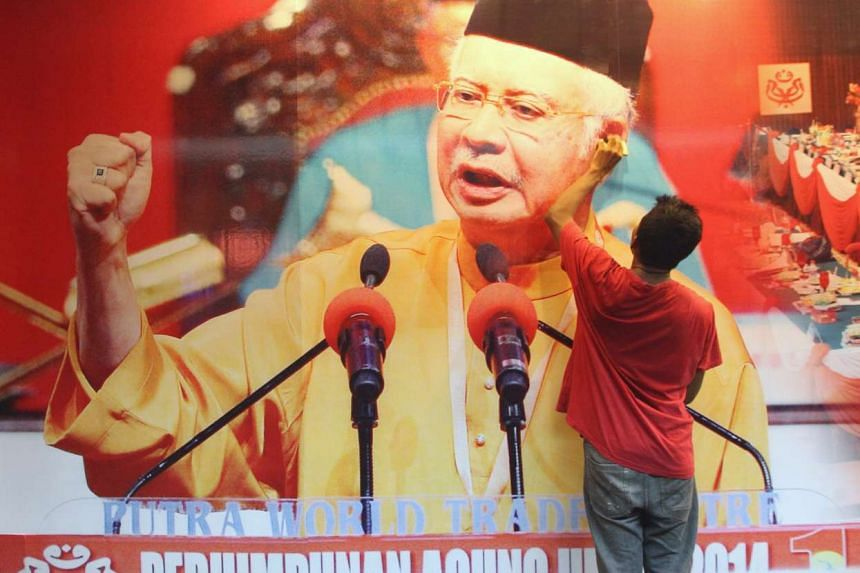 A worker putting up a poster of Prime Minister Najib Razak for the Umno general assembly meeting at Putra World Trade Centre (PWTC) in Kuala Lumpur.