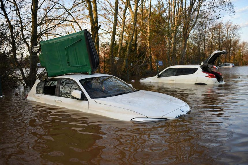 Vehicles stand submerged in flood waters, one with an industrial waste bin on its roof, in the car park of Carlisle United Football Club in Carlisle, north west England on Dec 7, 2015, after heavy flooding caused by Storm Desmond.