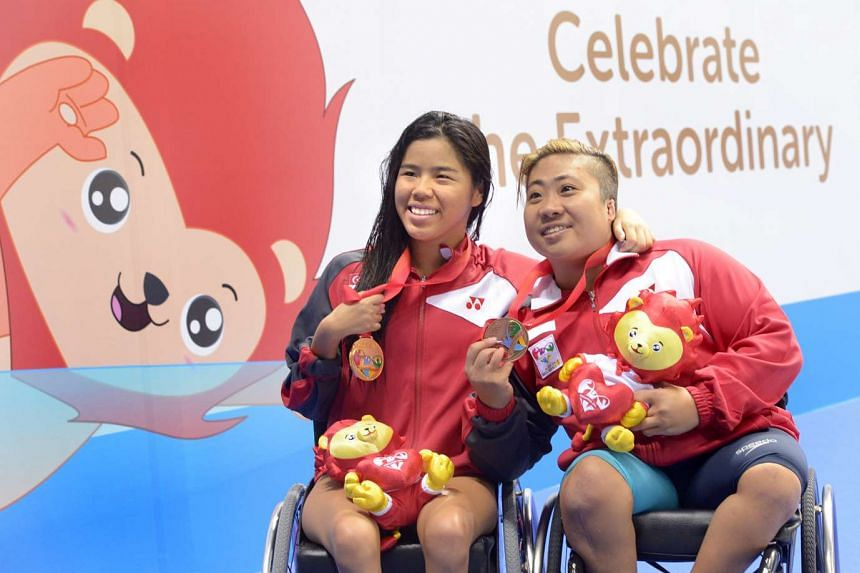 Yip Pin Xiu (left) and Theresa Goh at the victory ceremony on Dec 8, 2015.
