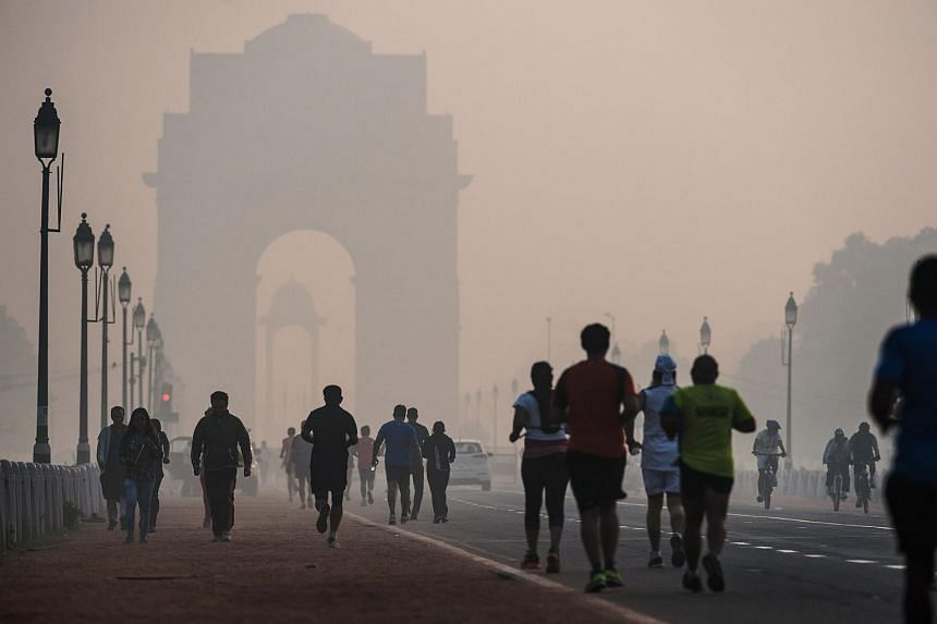 Joggers exercise on a smoggy morning near the India Gate monument in New Delhi.