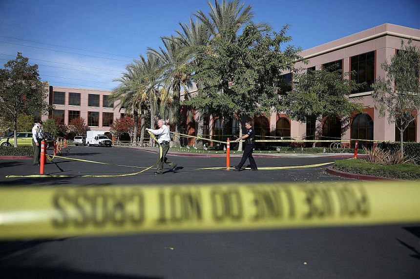 Officials put up police tape in front of the builiding at the Inland Regional Center in San Bernardino, California.
