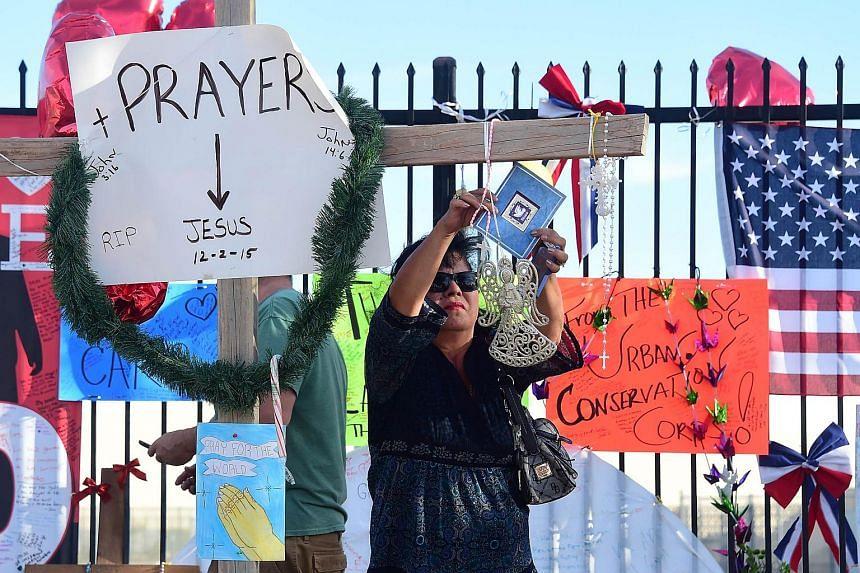 Teresa Calvillo hangs a card on a cross at a makeshift shrine near the scene of the shootings in San Bernardino, California.