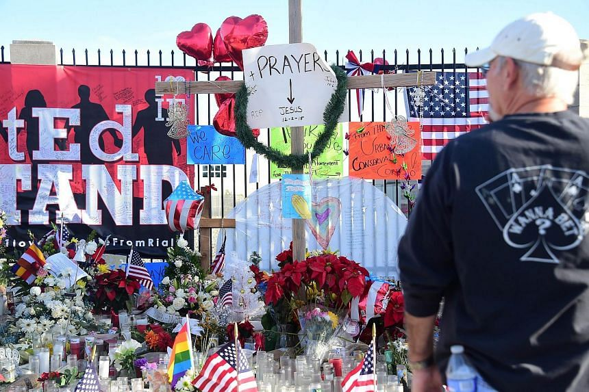 People pay their respects at a makeshift shrine near the scene of the shootings in San Bernardino, California.