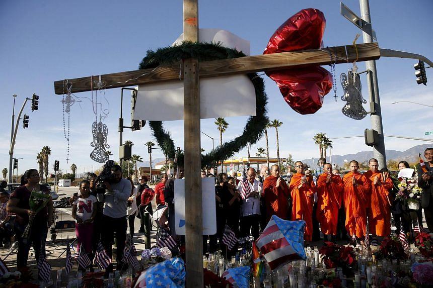 Monks with the Khmer Buddhist Society of San Bernardino pray at a makeshift memorial in San Bernardino, California.