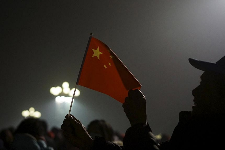 A visitor waves the Chinese national flag as people wait for a flag raising ceremony at the Tiananmen Square amid heavy smog in Beijing, China, on Dec 1, 2015.