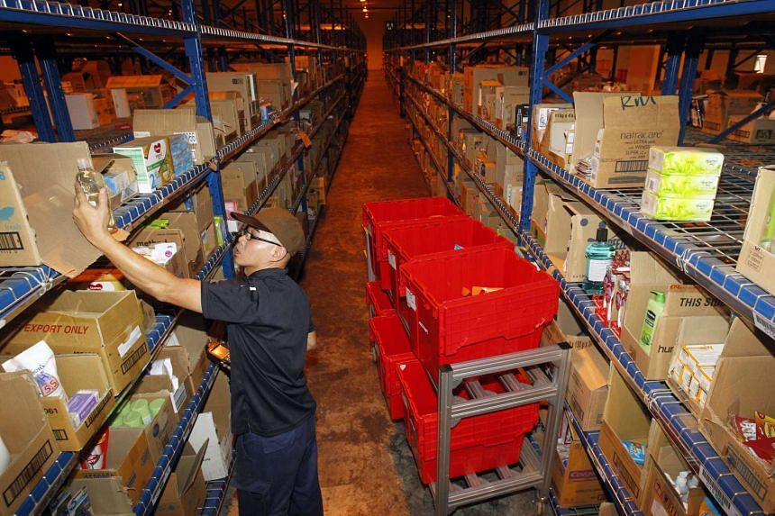 A worker picking grocery items at local online grocery retailer RedMart's warehouse.