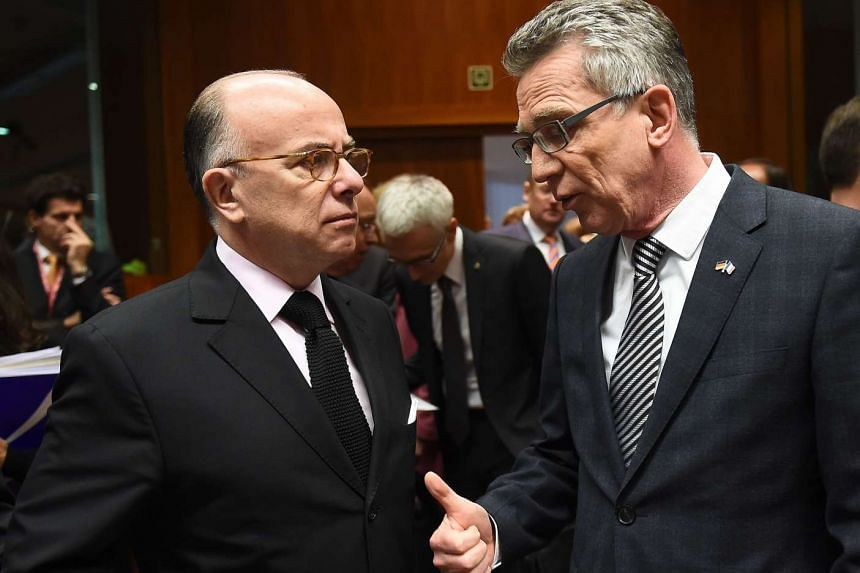 French Interior Minister Bernard Cazeneuve (left) speaks to German Interior Minister Thomas de Maiziere at the European Council in Brussels on Nov 20, 2015.
