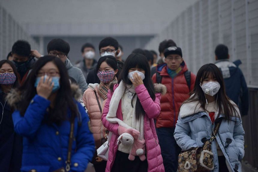 Pedestrians wearing face masks walk amid heavy air pollution in Beijing on Dec 8, 2015.