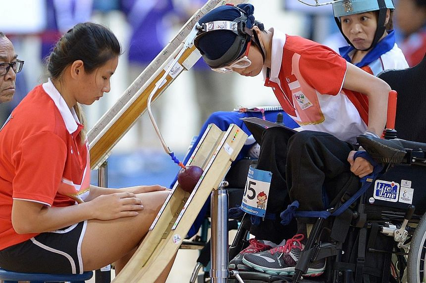 Toh Sze Ning using an assistive device to propel the ball. She led 2-0 against Thai Paralympian Tanimpat Visaratanunta but could not close out the final and lost 2-3.