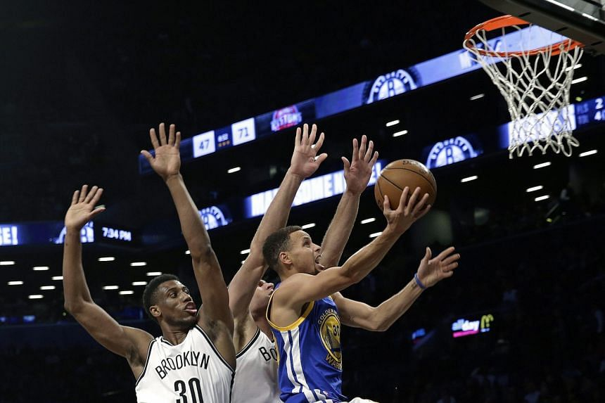 Stephen Curry (right) of the Golden State Warriors drives past Brooklyn Nets opponents Thaddeus Young (No. 30) and Brook Lopez during the Warriors' 114-98 victory at the Barclays Center on Sunday.