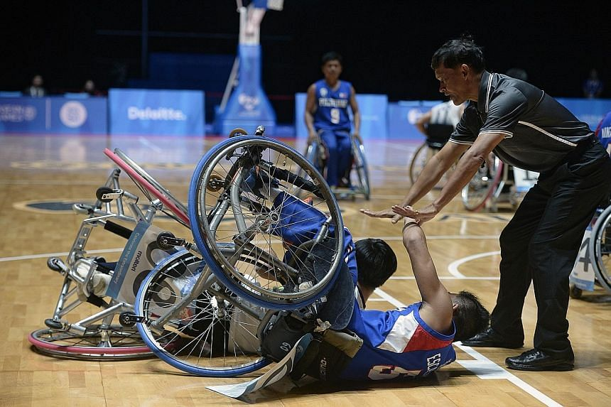 An official tends to Paphatsalang Khammany of Laos and John Rey Aguirre Escalante (in blue) of the Philippines after they collided during their match yesterday. The Philippines won a spirited encounter 61-55.