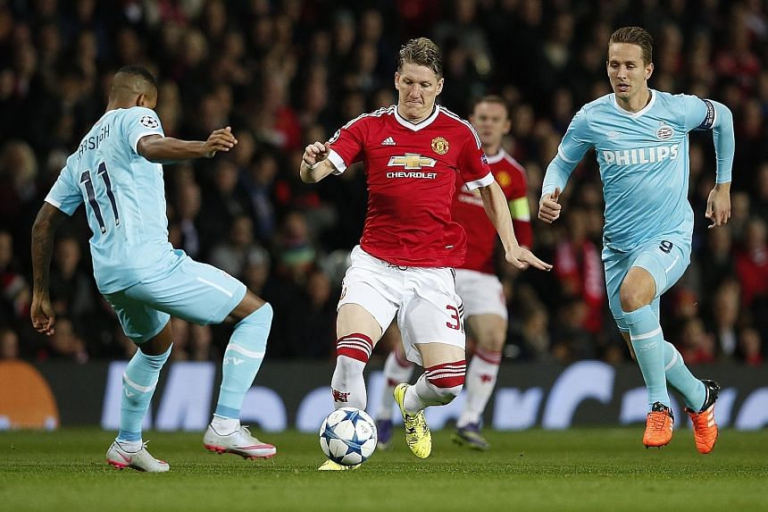 Manchester United midfielder Bastian Schweinsteiger (centre), holding off PSV Eindhoven's Luciano Narsingh (left) and Luuk de Jong.