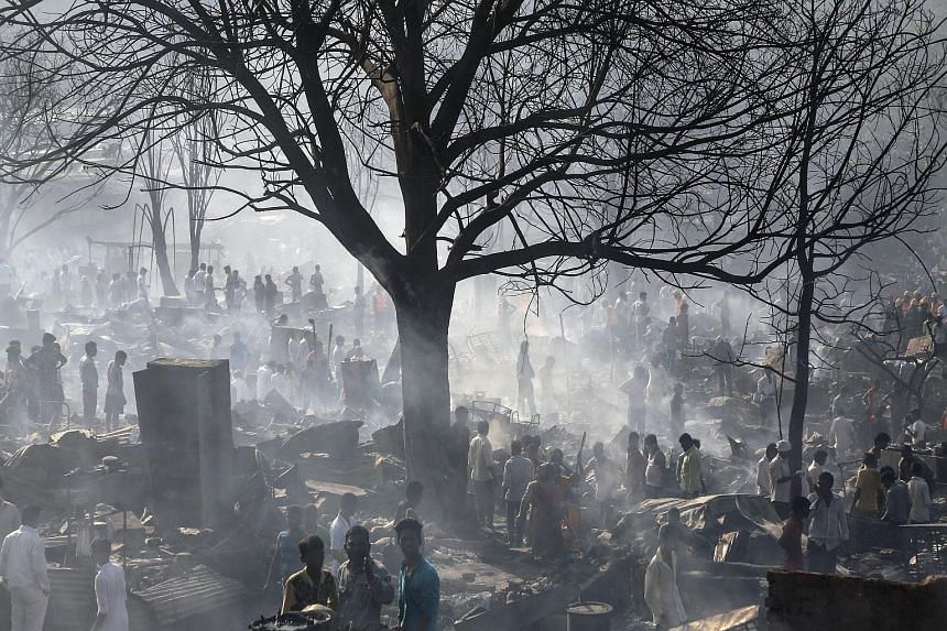 People sifting through the wreckage after a massive fire broke out in the slums of Damu Nagar in the Kandivali area of Mumbai, India, yesterday. The fire destroyed around 1,000 shanties and killed at least two people, while at least four others were