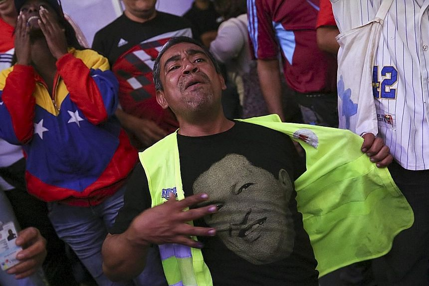 Supporters of Venezuela's defeated government, including this man wearing a T-shirt with an image of the late socialist president Hugo Chavez, were left distraught by the election result.