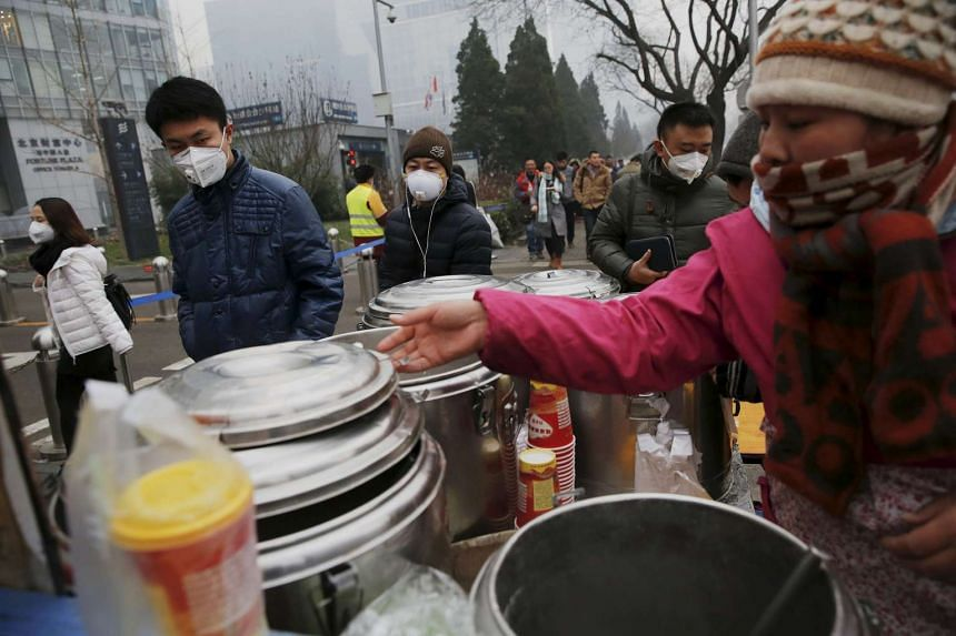 Morning commuters wearing protective masks passing by a food vendor in central Beijing on Dec 8, 2015.