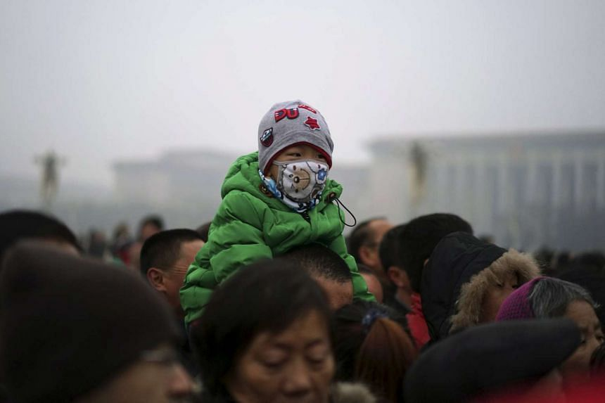 A boy wearing a mask sitting on the shoulders of a man as they watch a flag-raising ceremony amid heavy smog at the Tiananmen Square in Beijing, China, on Dec 8, 2015.