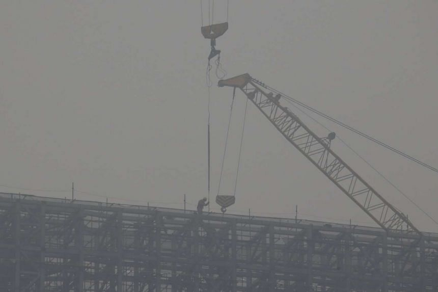 A labourer working at the construction site of a business building amid heavy smog in central Beijing on Dec 8, 2015.