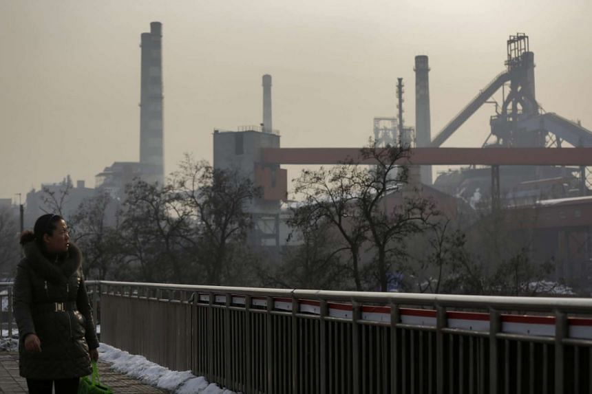A woman looks at a thermal power plant on a hazy day on the outskirts of Beijing on November 2015.