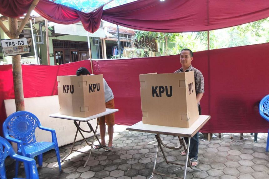 Voters in South Tangerang regency, on the outskirts of Jakarta, cast their ballot to vote for one of the three eligible pairs of reagents and deputy reagents.