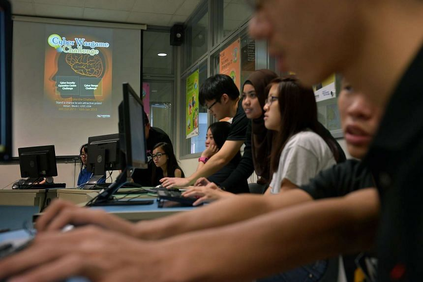 Students helping visitors attending the polytechnic's open house play a cyber security game.