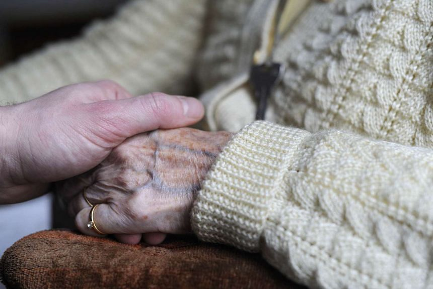 A picture taken on March 18, 2011 shows a woman suffering from Alzheimer's disease holding the hand of a relative in a retirement house in Angervilliers, eastern France.