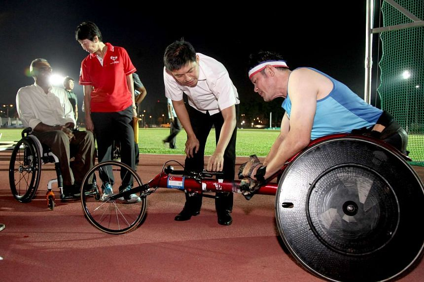 Minister for Social and Family Development and also the president of the Singapore National Olympic Council Tan Chuan-Jin (second from right) speaking to Jack Lai (right) during his visits at the Kallang Practice track.