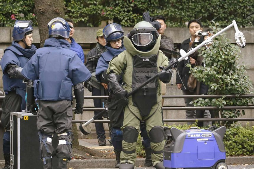 Members of a police bomb disposal squad near the site of an explosion at the Yasukuni shrine in Tokyo on Nov 23.