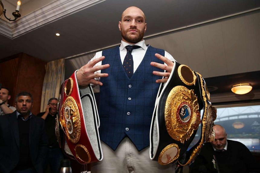 Tyson Fury poses with his belts after a press conference at The Whites Hotel, Bolton.