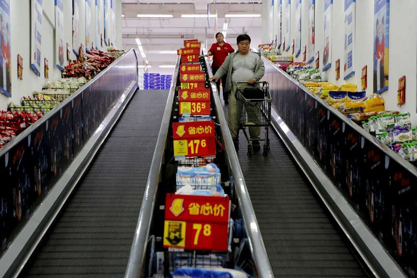Shoppers ride on a travelator at a supermarket in Beijing, China.