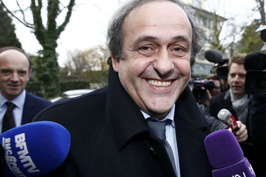 UEFA President Michel Platini smiles as he arrives with his counsel Thomas Clay (left) for a hearing at the Court of Arbitration for Sport (CAS) in Lausanne, Switzerland on Dec 8, 2015.