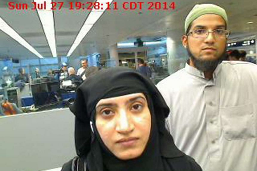 Tashfeen Malik (left), and Syed Farook are pictured passing through Chicago's O'Hare International Airport in this July 27, 2014 handout photograph.