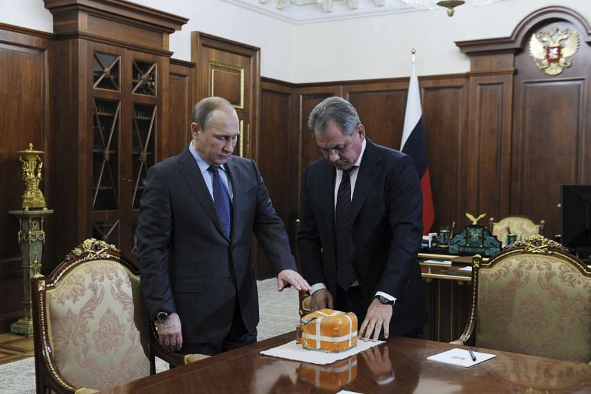 Russian Defence Minister Sergei Shoigu (right) presents to President Vladimir Putin the parametric flight recorder of the downed SU-24 jet.