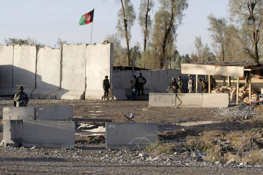 Afghan security forces stand guard at the entrance gate of Kandahar Airport.
