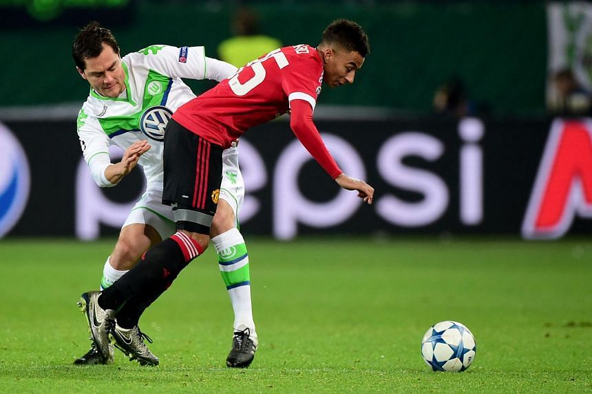 Manchester United's Jesse Lingard (right) and Wolfsburg's Marcel Schaefer fight for the ball during the Uefa Champions League Group B football match.