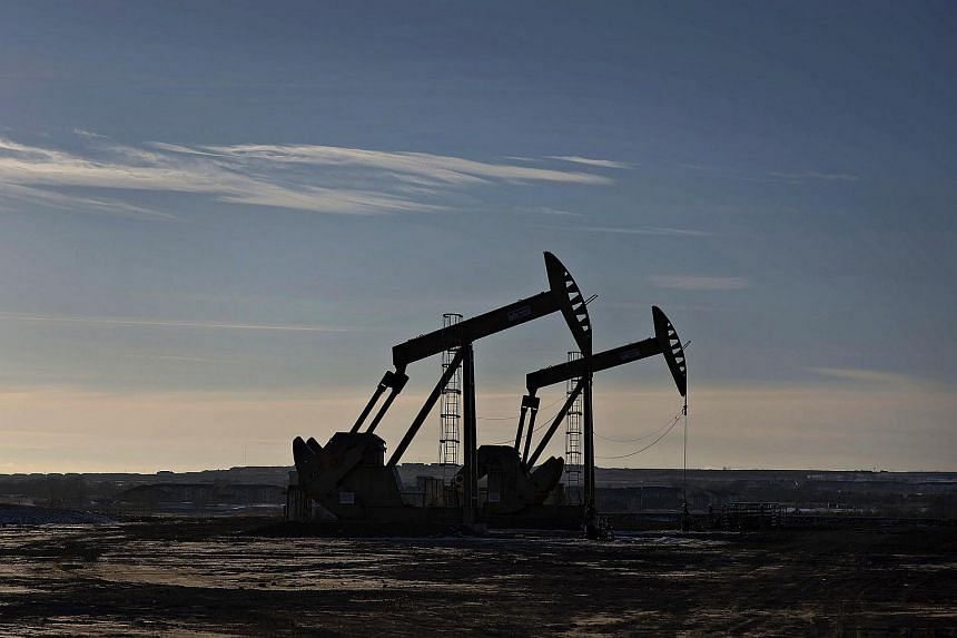 The silhouette of pumpjacks is seen on the site of an oil well outside Williston, North Dakota.