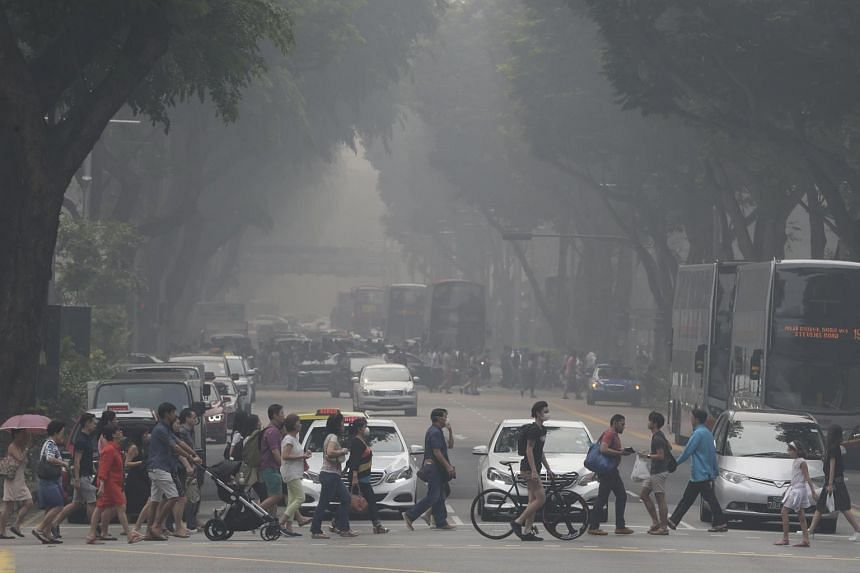 Pedestrians crossing a road in Orchard amid a view obscured by haze on Sept 24, 2015.