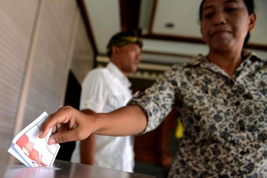 A woman casting her vote at a polling station in Kuta, Bali, on Dec 9.