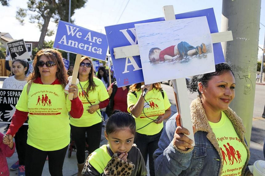 People holding signs supporting Syrian refugees and increased immigration into the US during a procession in Los Angeles on Nov 25.