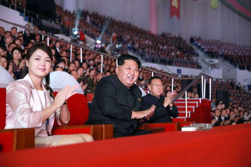 Kim Jong Un (centre), accompanied by his wife Ri Sol Ju, enjoying a performance.
