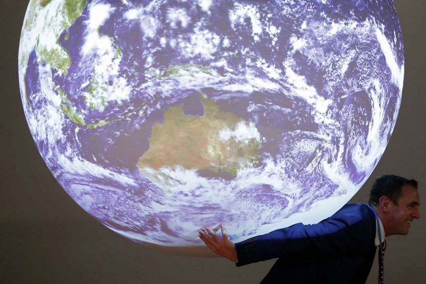 A participant poses with a replica of the planet during the World Climate Change Conference 2015 (COP21).
